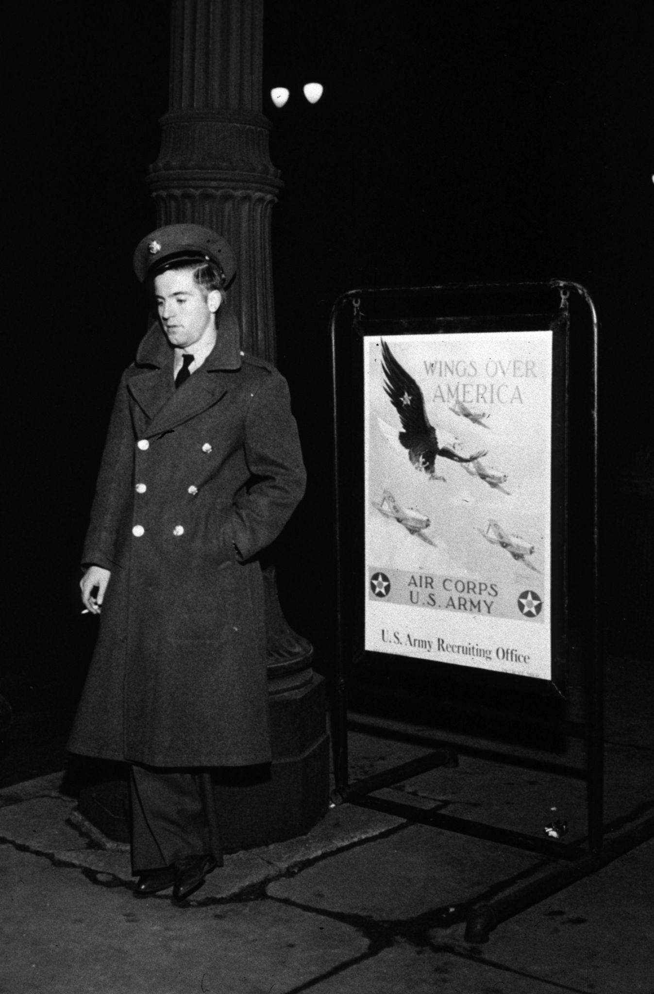 1941. Солдат стоит у вербовочного плаката в Детройте, штат Мичиган, в канун Нового года..jpg