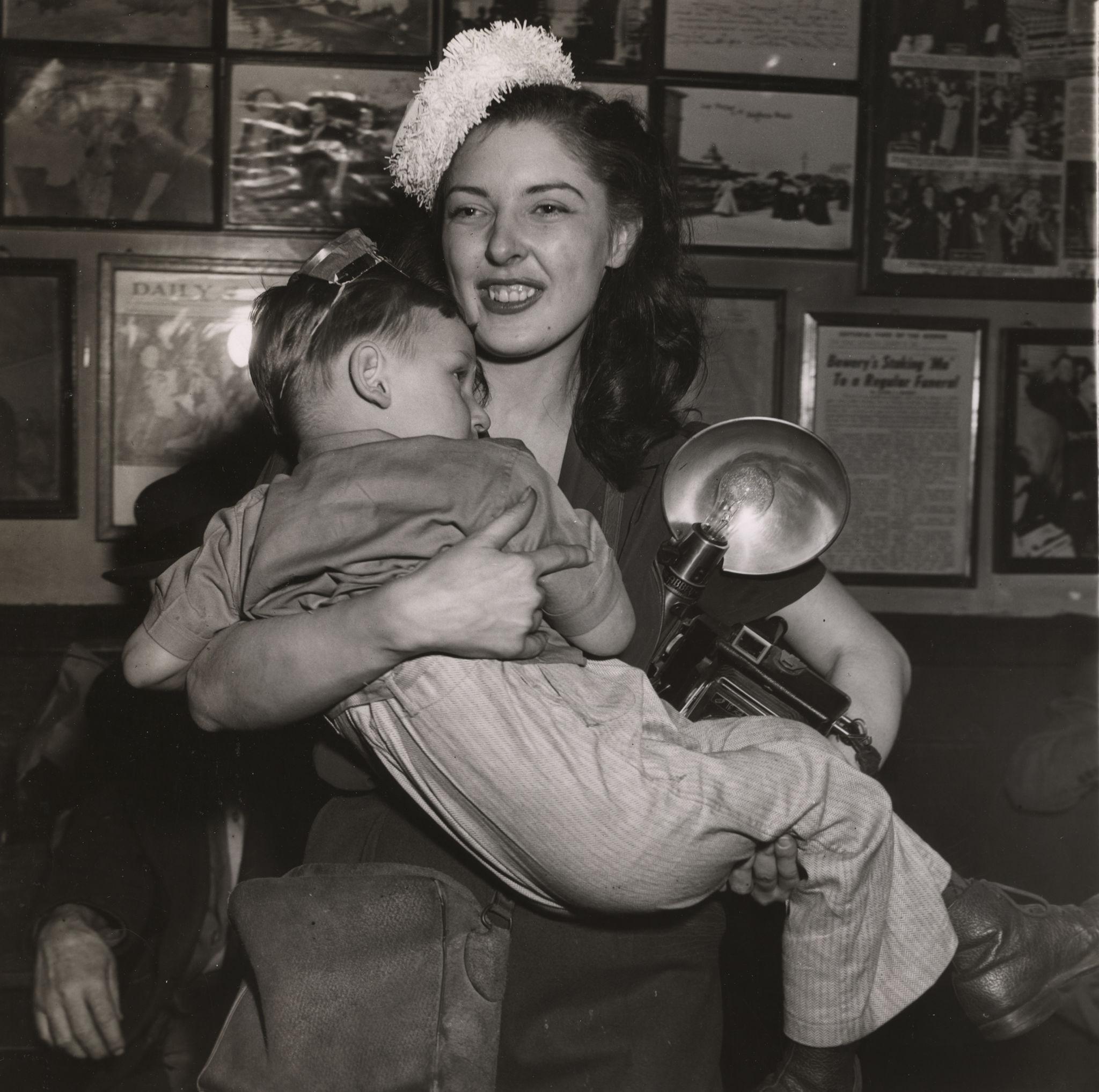 1943. Женщина несет ребенка и камеру со вспышкой в канун Нового года, Нью-Йорк.jpg