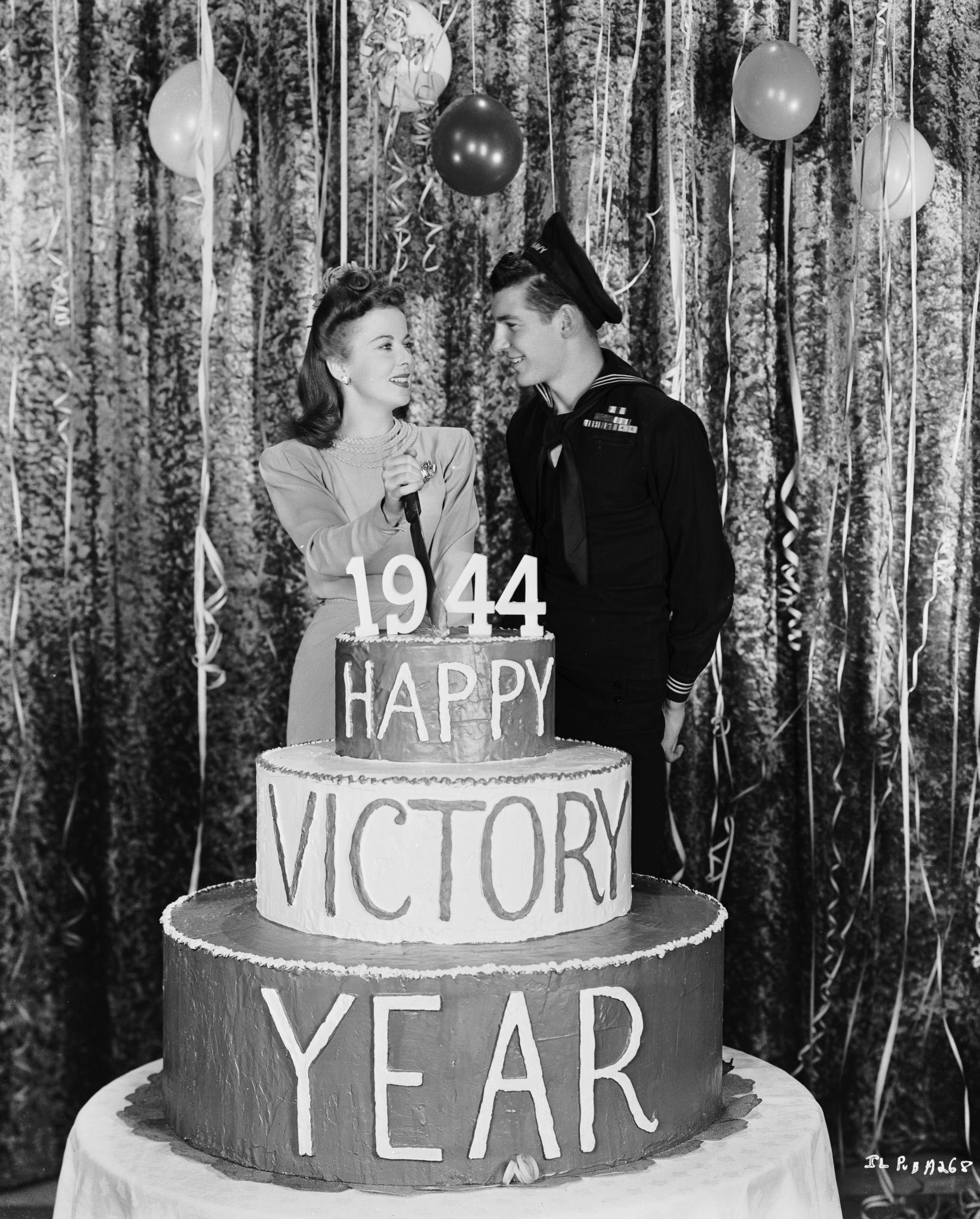 1944. Британская актриса Ида Лупино улыбается моряку, разрезавшему торт с надписью «Счастливый год победы»..jpg