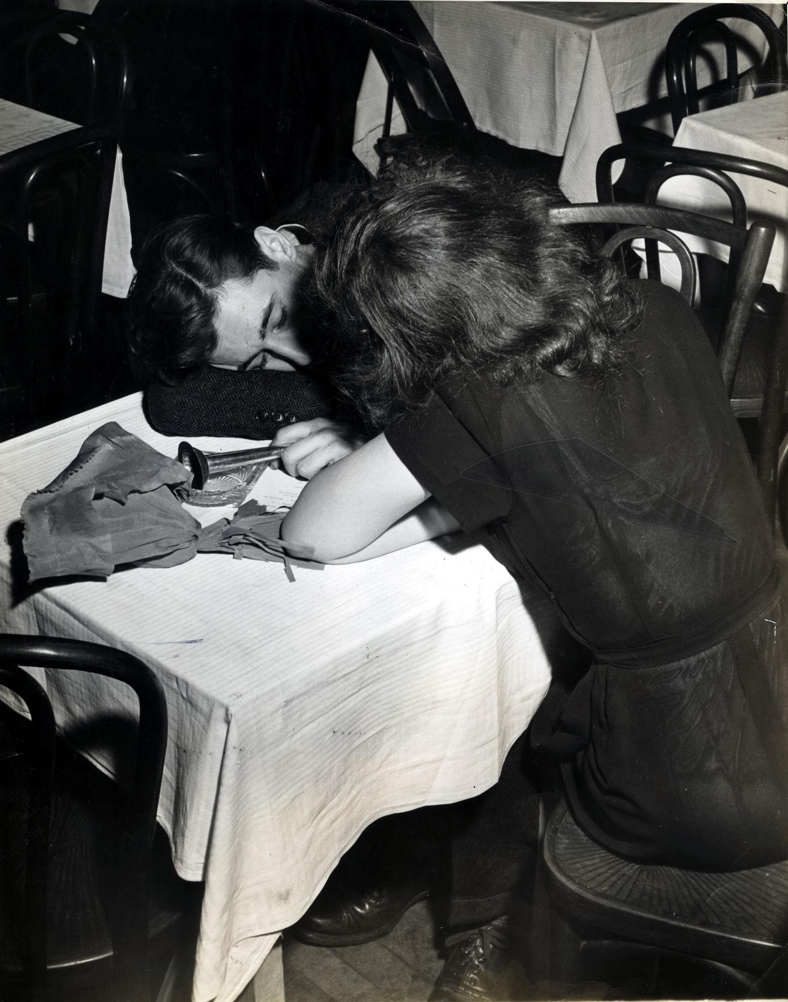 1945. Женщина сидит со спящим мужчиной за столом в Казино Stuyvesant на углу 2-й авеню и 9-я улица после новогодних праздников.jpg
