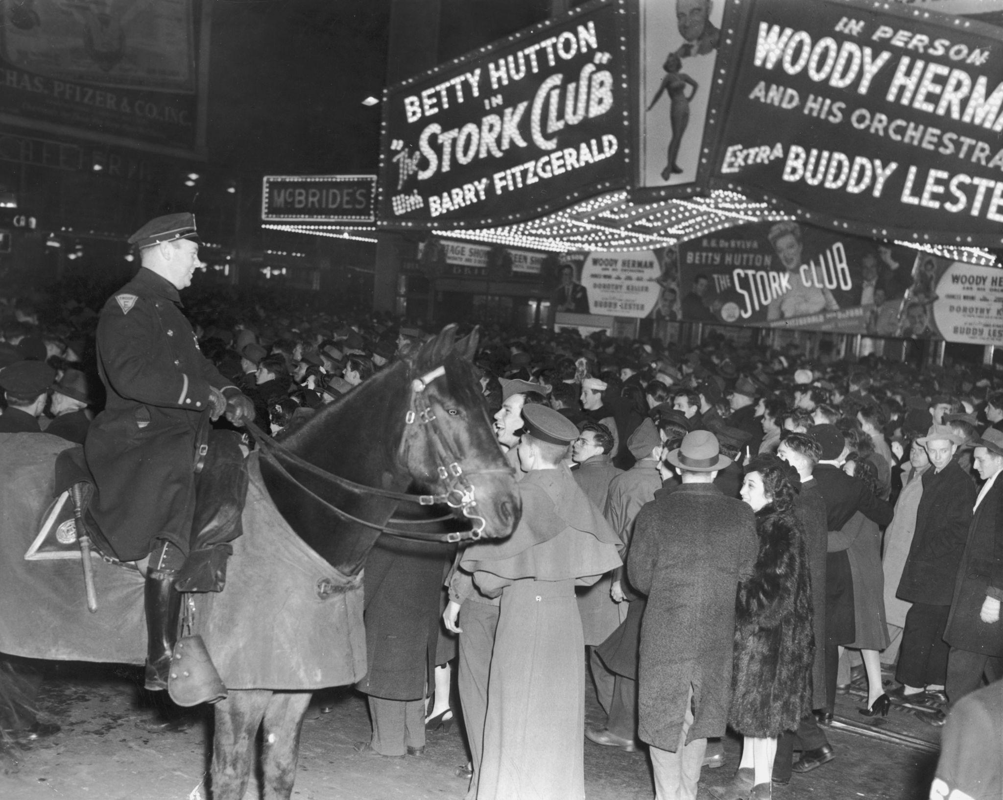 1946. Толпы собираются под рекламным плакатом фильма режиссера Хэла Уокера «Клуб аистов» ночью на Бродвее на Таймс-сквер в Нью-Йорке в канун Нового г…