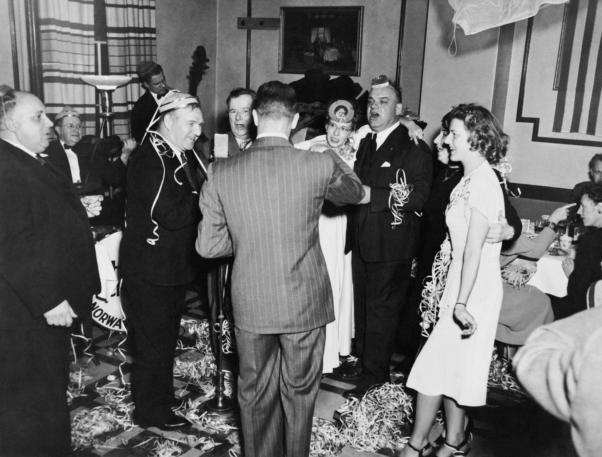 1948. Группа людей на новогодней вечеринке в отеле Stone поет и веселится.jpg
