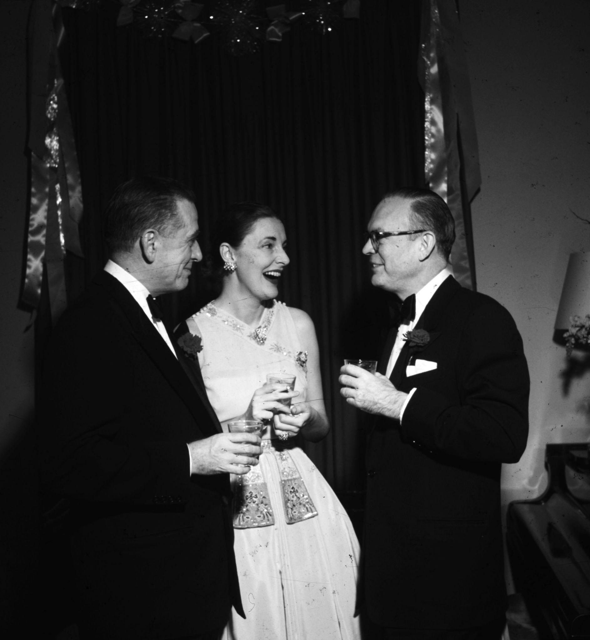 1952. Леланд Хейворд и его жена Слим (урожденная Нэнси Гросс, бывшая жена Говарда Хоукса) беседуют с издателем Гарднером Коулзом-мл. на новогодней ве…