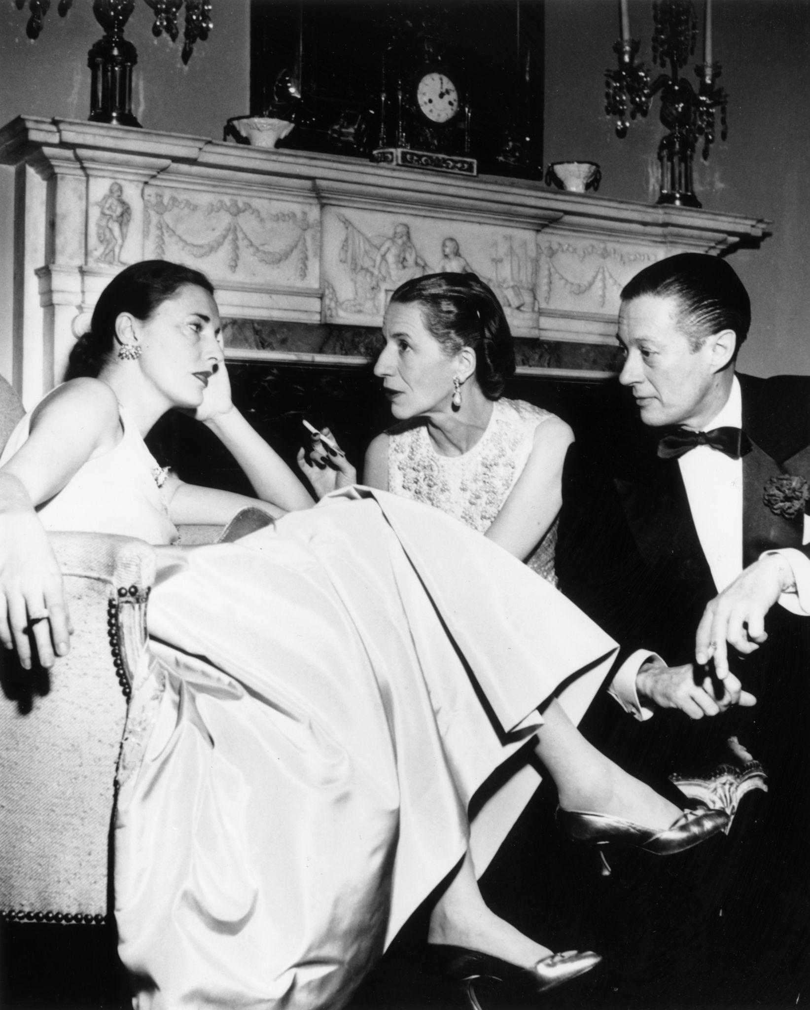 1952. Слим Хоукс (бывшая жена режиссера Говарда Хоукса) беседует с редактором Vogue Дианой Вриланд и ее мужем Ридом на новогодней вечеринке.jpg