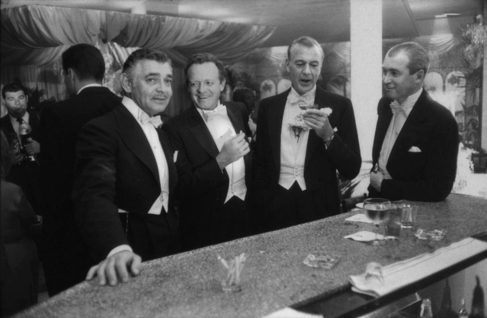 1957. Кларк Гейбл, Ван Хефлин, Гари Купер и Джеймс Стюарт наслаждаются шутками на новогодней вечеринке, которая проходит у Романовых в Беверли Хиллз.…