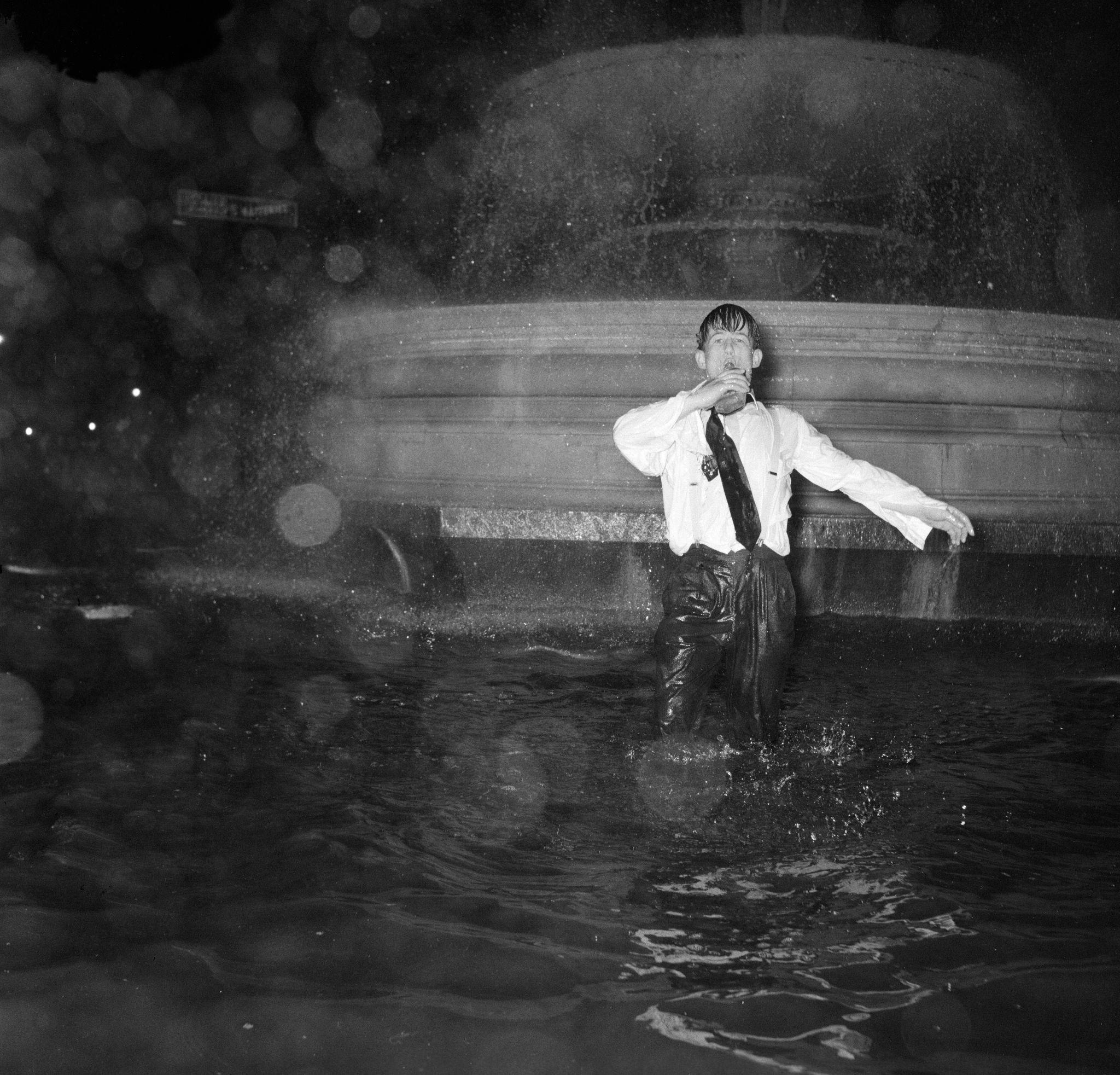 1960. Трафальгарская площадь.Тысячи людей собрались на площади, и многие пошли к фонтану, чтобы отпраздновать это Новый Год, 1 января (2).jpg