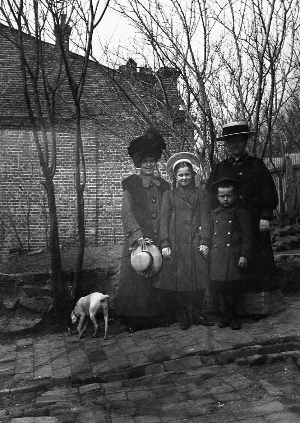Елена Александровна Захарина (с шляпкой в руках), её сын Андрей и знакомая женщина с дочкой во дворе дома по улице Пушкинской. 1910-е