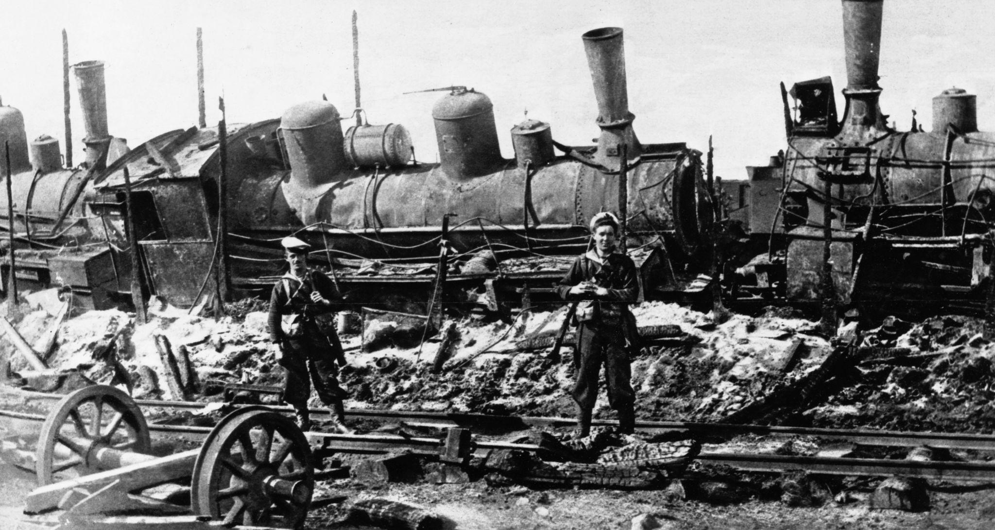 Два моряка Британского флота стоят на страже возле паровоза, поврежденного большевиками на станции Сарока