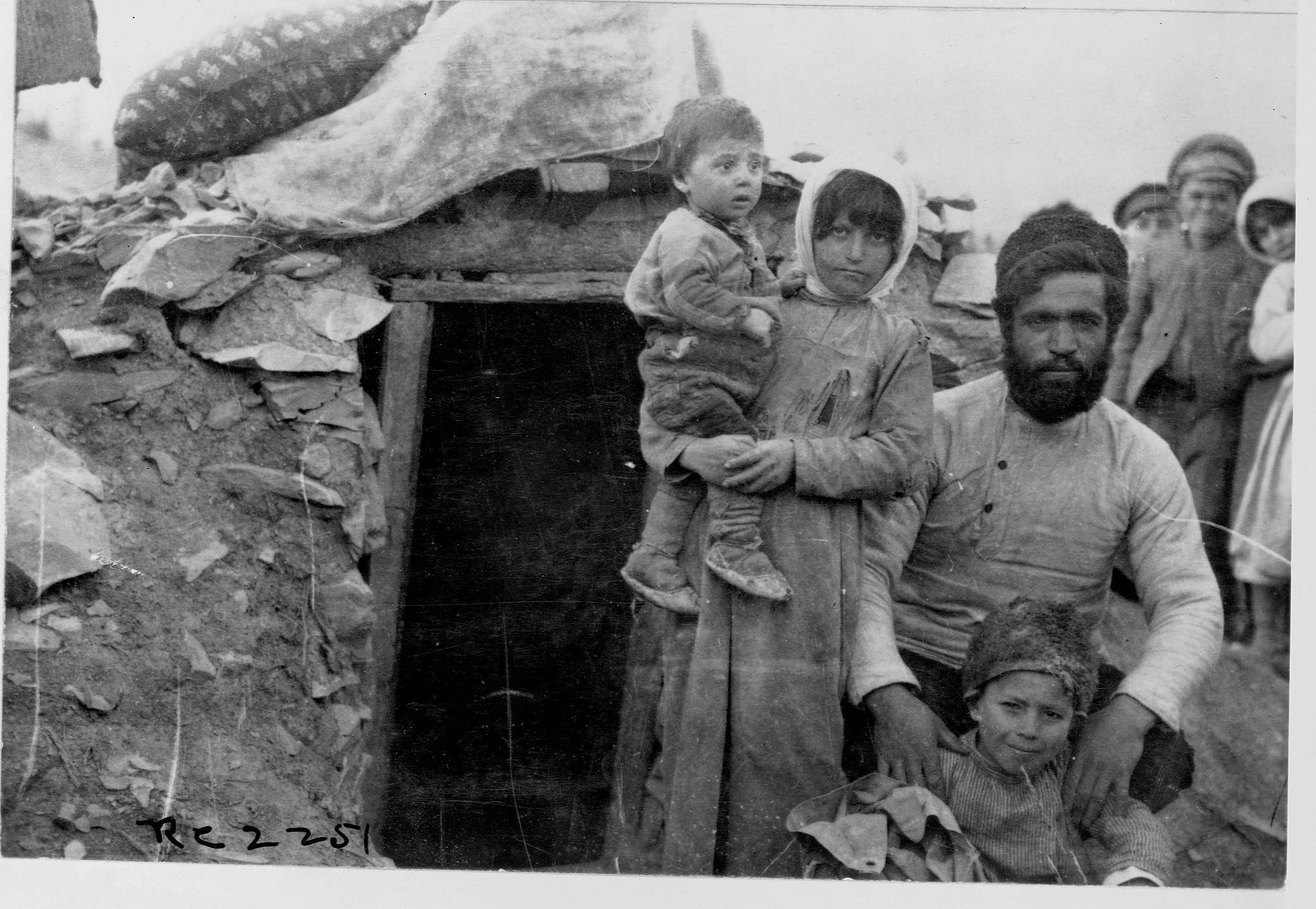 Семья беженцев стоит возле своей землянки в Новороссийске