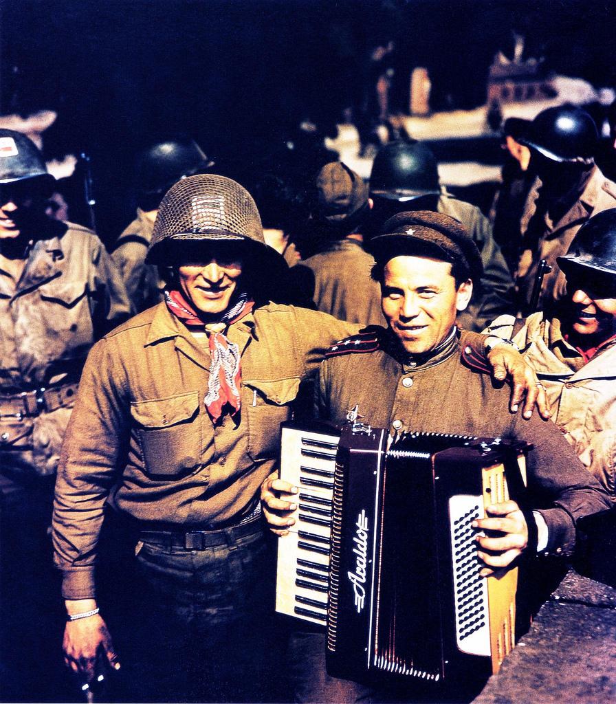 Русский солдат с баяном позирует с американским солдатом во время встречи солдат обеих армий в Торгау. 25 апреля 1945