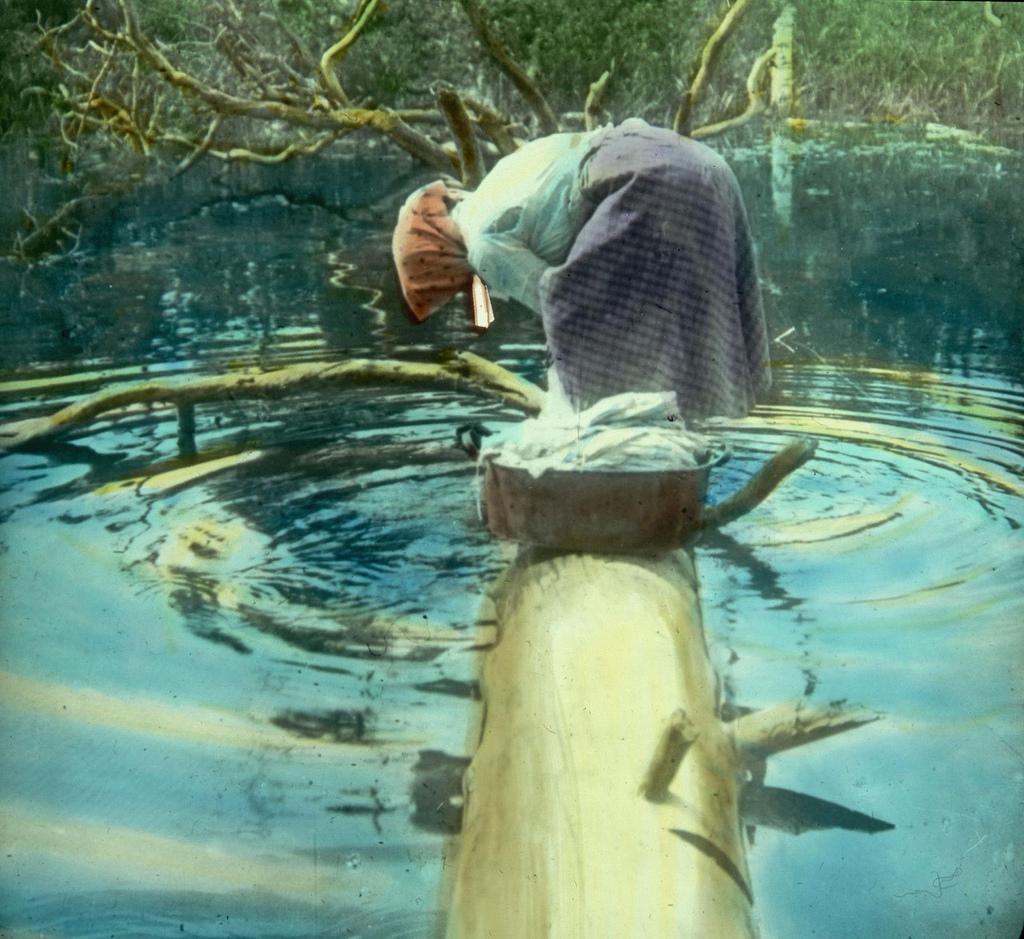Крестьянка стоит на упавшем бревне над ручьем и стирает белье