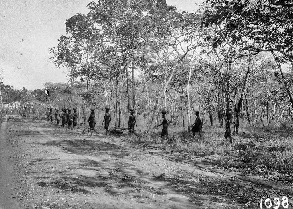 Окрестности Исоки. Женщины на проселочной дороге, несущие груз на головах