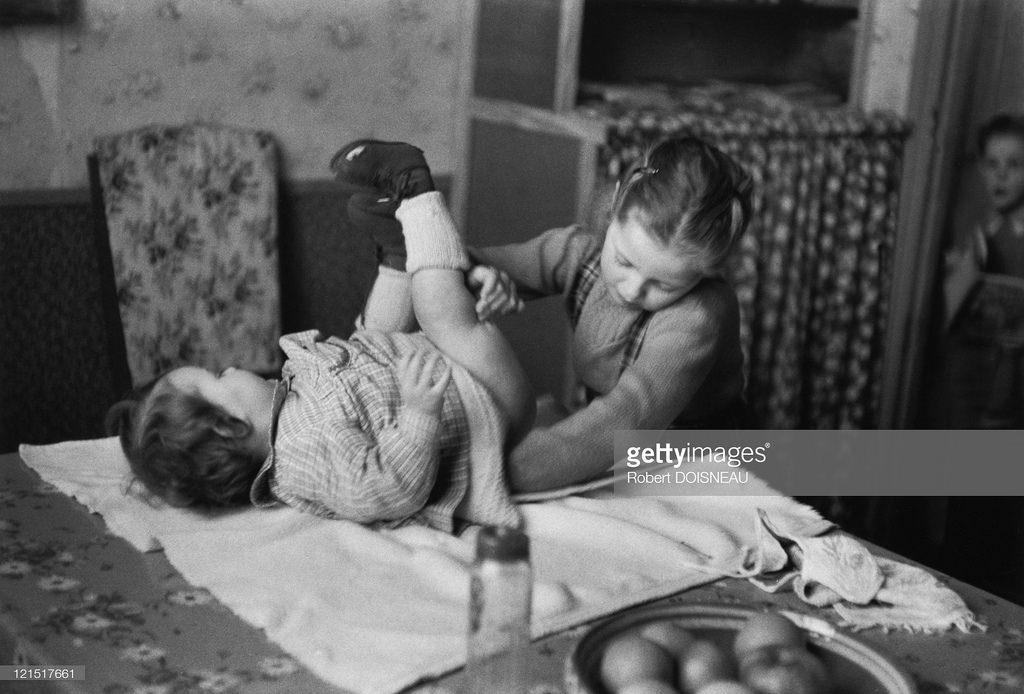 1955. Семейная жизнь. Маленькая девочка, меняющая подгузник ребенку