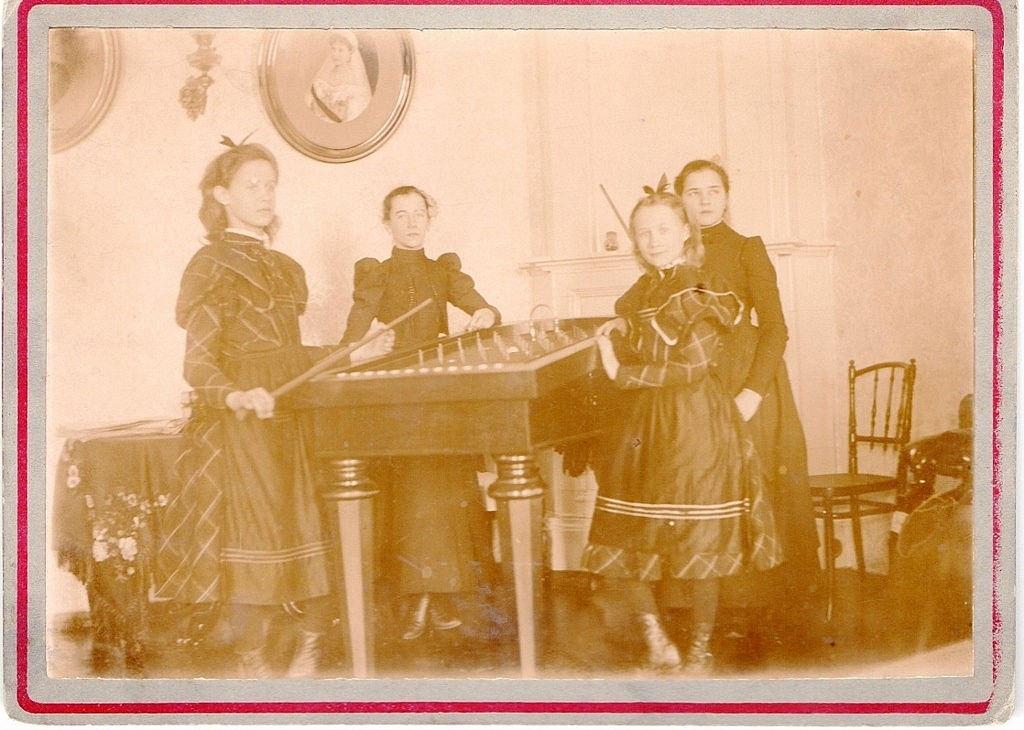 1896. Гостиная в губернаторском доме в Могилеве. Вер. Ник. и Мар. Ник. Зиновьева (играют в Трик-Трак). На стене портрет Мар. Фед., перед которым Манечка делала извинительные реверансы, когда «мазала», играя на рояле