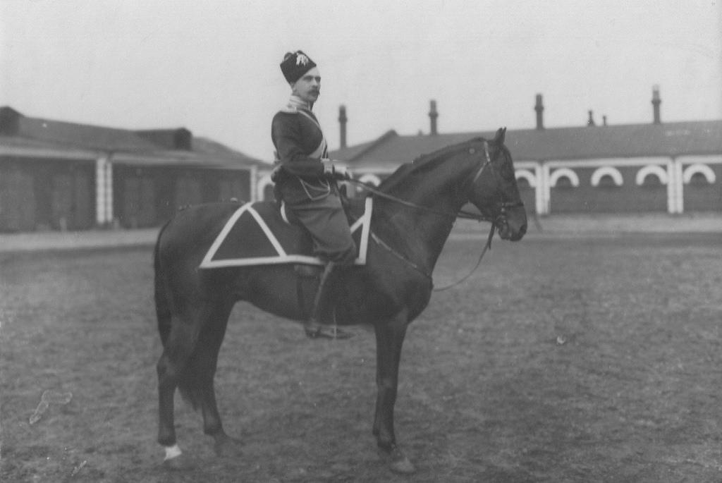Казачий офицер на коне во дворе казарм в парадной форме. 21 августа 1913