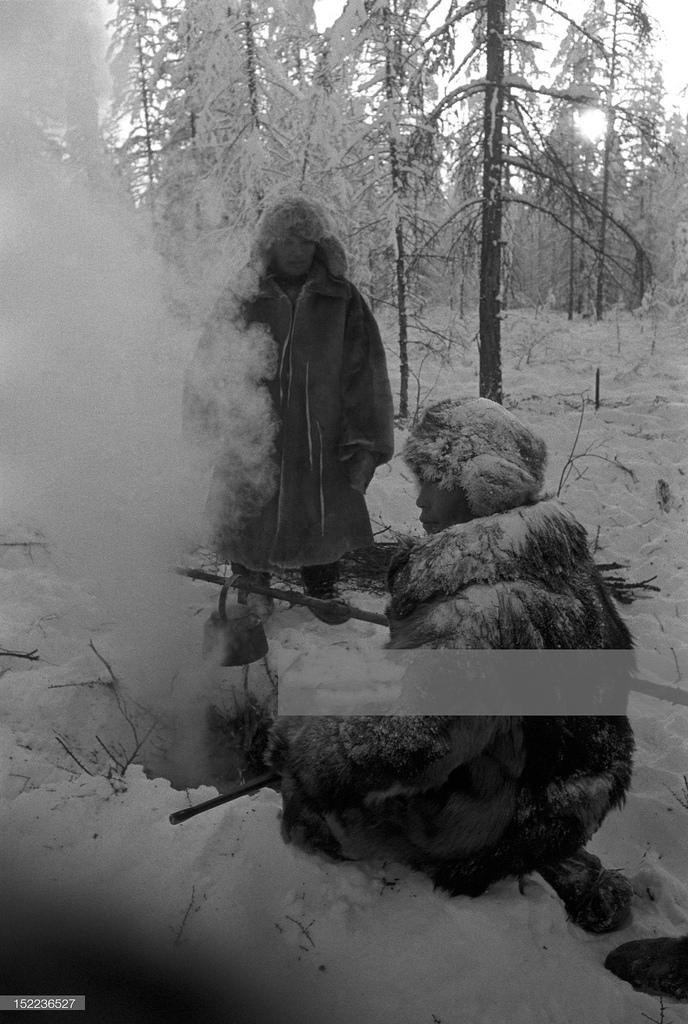 Якутия. Два якута-охотника разводят костер в сибирской тайге