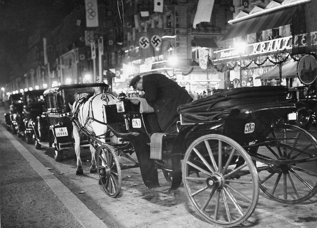 1936. Кэб, ожидающий между припаркованными автомобилями перед кафе «Кранцлер» на Унтер-ден-Линден, 25 в ночное время