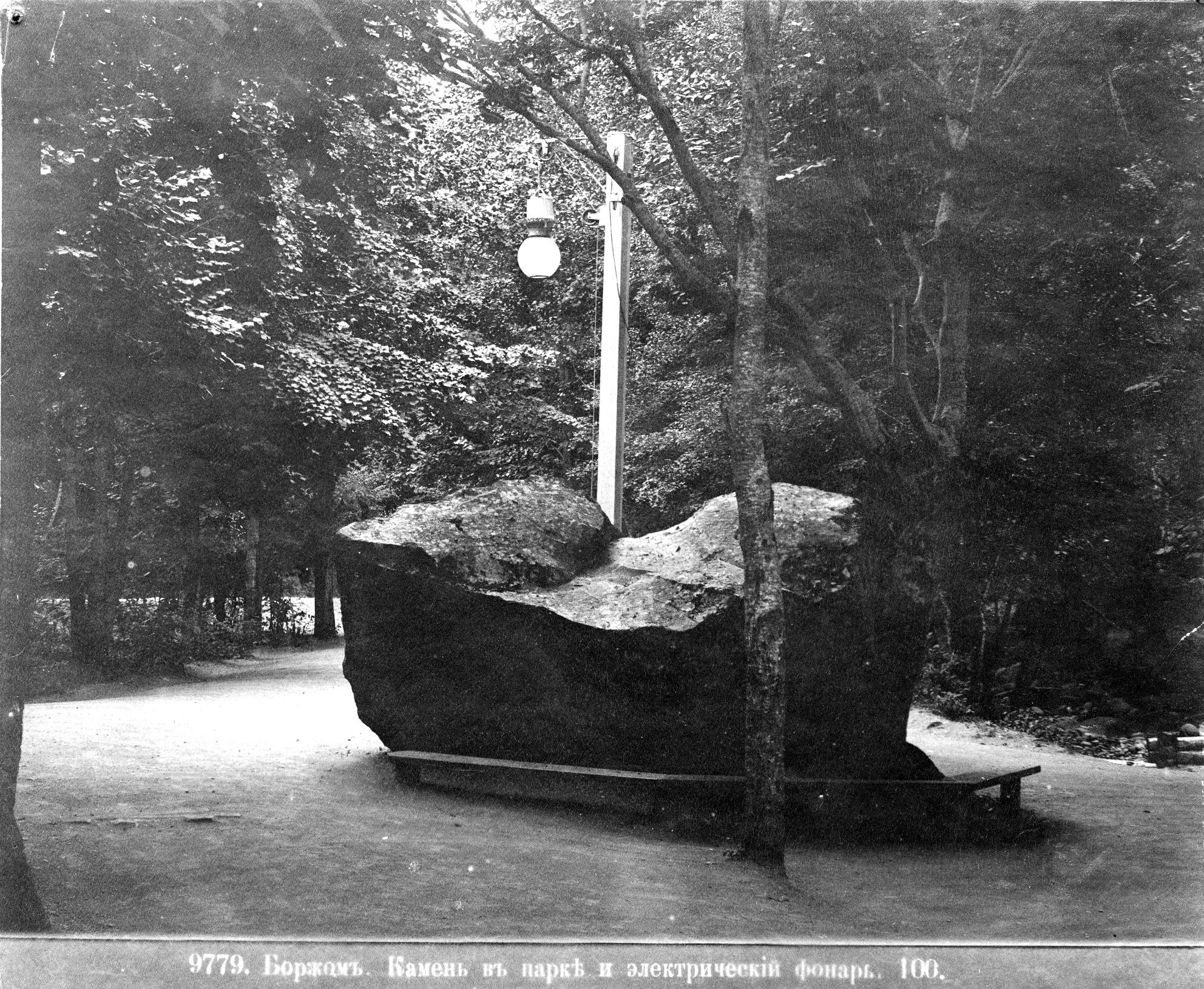 Камень в парке и электрический фонарь