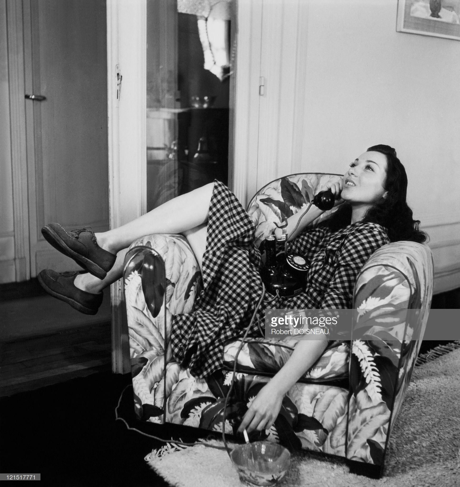 1950. Женщина в кресле разговаривает по телефону