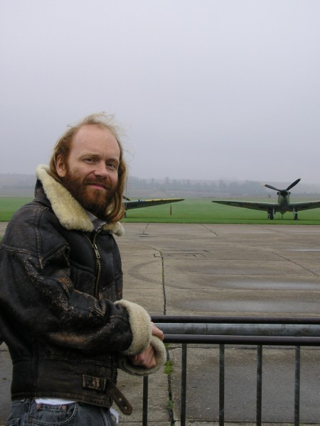 Nick, a man with long ginger hair and beard, standing in a leather jacket in front of two 1940s warplanes.