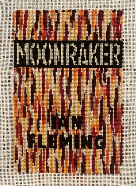 Cross stitch version of a book cover showing red and yellow flames, with 'Moonraker' and 'Ian Fleming' in block capitals.