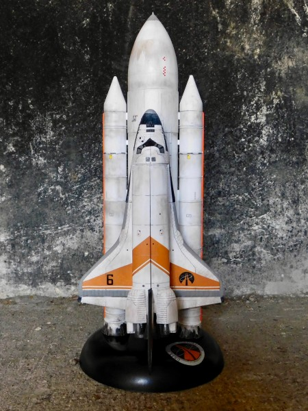 Model Moonraker 6 space shuttle and booster rockets displayed against a blackened concrete wall.