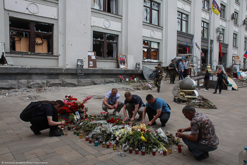Люди несут цветы погибшим, июнь 2014