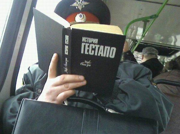 полицейский читает Историю гестапо