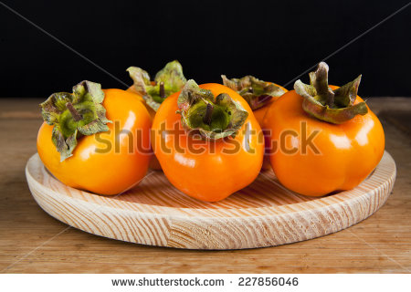 stock-photo-fresh-ripe-persimmon-on-a-wooden-table-227856046
