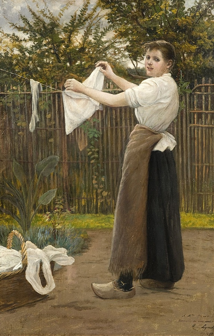 Девушка развешивает одежду в саду