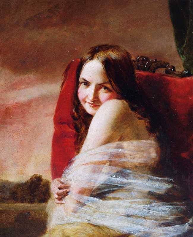Молодая женщина, сидящая на красной подушке
