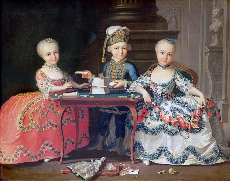 Мальчик и две девочки, строящие карточный домик