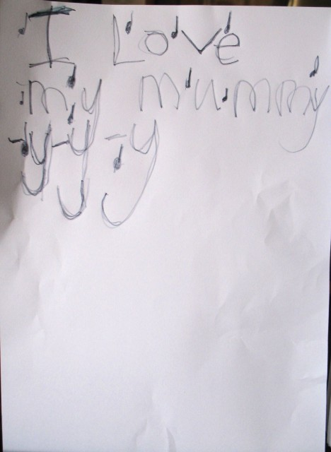 on the paper are the words 'I Love my mummy -y-y-y' with some note symbols drawn in various places close to the text.