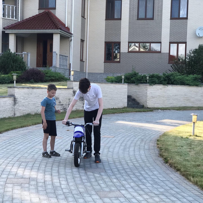 Старший учит младшего кататься на детском мотоцикле. Передаёт свою игрушку по наследству.