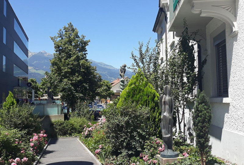Горы, прилизанные дома, дороги и тротуары, зелень, цветы, скульптуры.