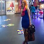 Red haired girl blue dress pink shoes scarf, red dress on poster / Рыжая девушка с розовым шарфом и туфлями и синем платье на фоне постера с красным платьем