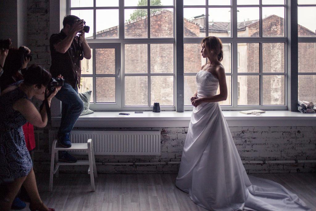 Many photographers and bribe white long dress open shoulders in studio / Фотографы и невеста в длинном белом платье в студии