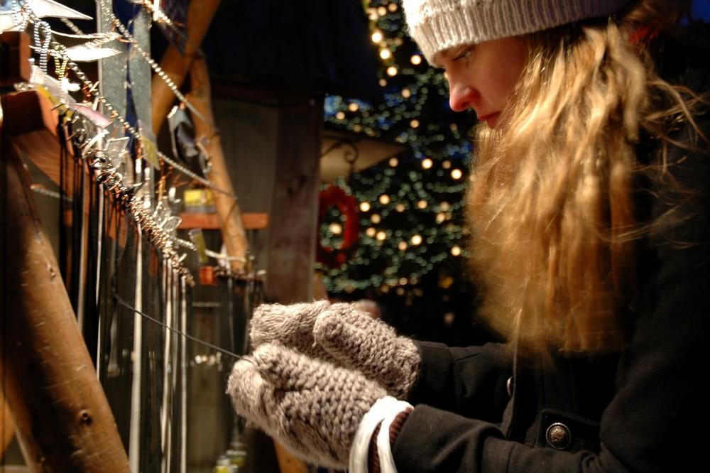 Девышка выбирает украшения на рождественской ярмарке в Таллине