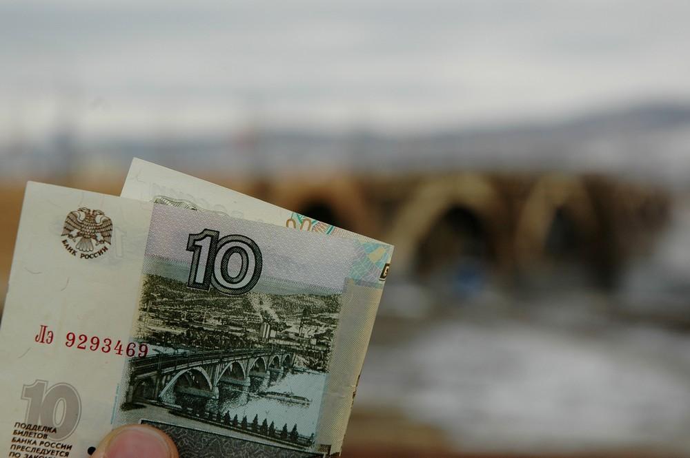 Десятирублевая купюра на фоне моста через Енисей в Красноярске