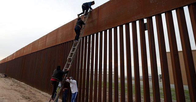 иммигранты перелезают по лестнице через забор на границе с Мексикой