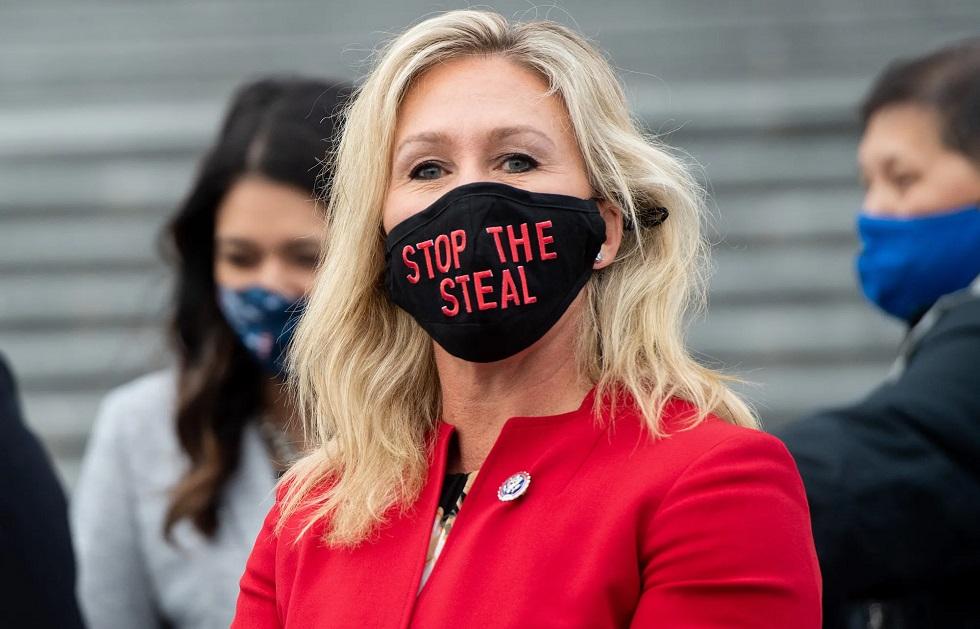 Тейлор Грин в маске, на которой написано прекратить воровство