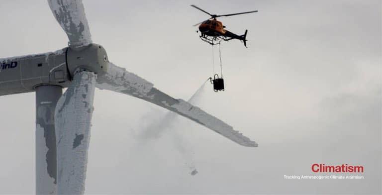 Вертолёт распыляющий жидкость на лопости ветряной турбины