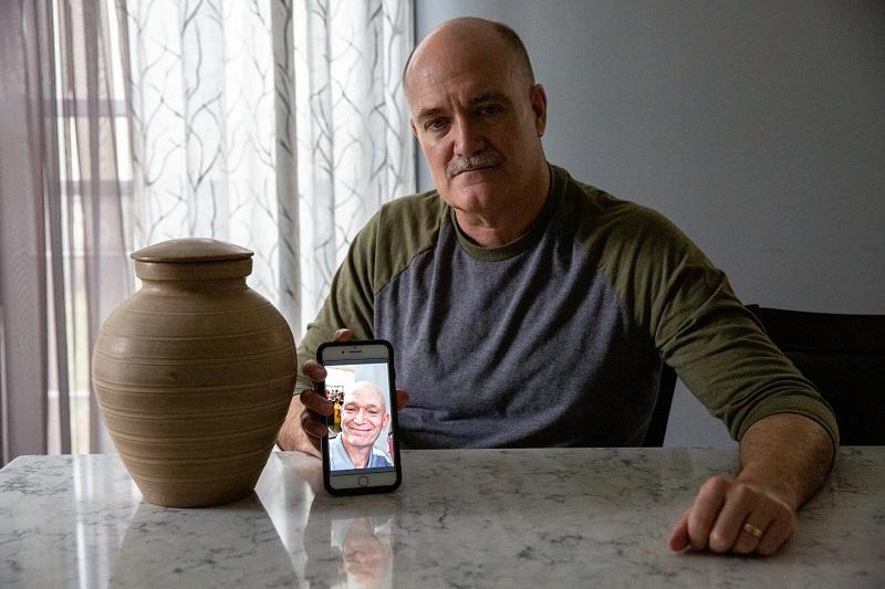 Рассел Блатт показывает телефон с фотографией своего брата Стейси, который умер от рака