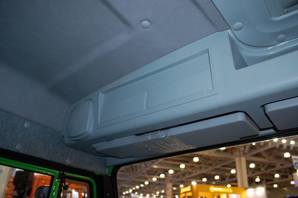 Над ветровым стеклом расположена удобная полка для водительского скарба, с заготовкой под 1DIN магнитолу с динамиками, тахограф над водителем и закрывающийся вещевой отсек справа