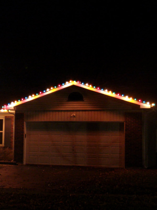 A string of coloured lights along the roofline of a house
