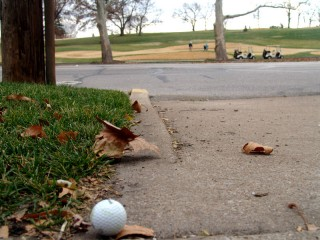 A golf ball in a driveway across the street from a golf course