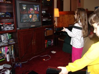 Two small children playing Guitar Hero