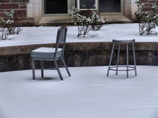 A chair and a stool topped with snow