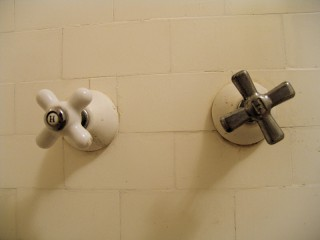"Two shower valves marked ""H"" on a wall"