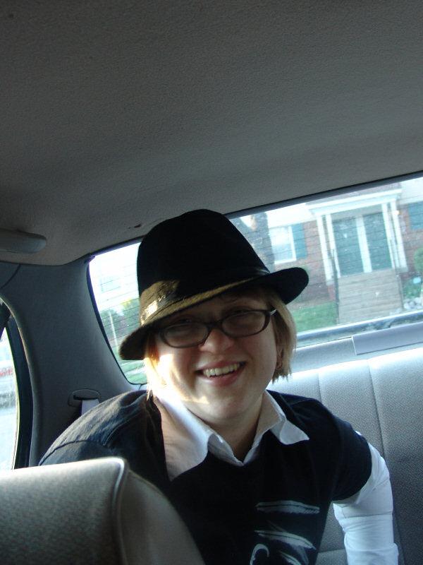 Hat-wearing backseat passenger of a car smiles